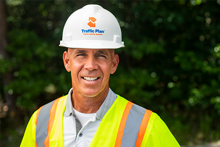 traffic plan employee posing in full company garb while standing in front of green bushes